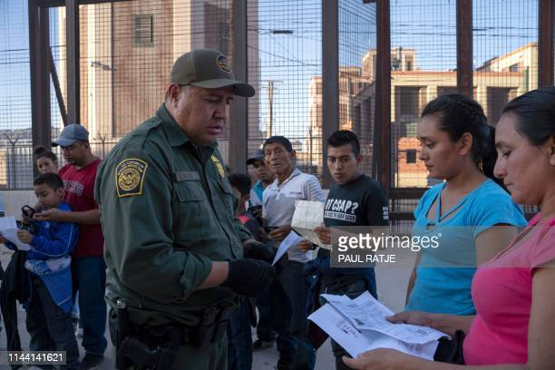 US Customs and Border Protection agent checks documents of a small group of migrants who crossed the Rio Grande from Juarez Mexico on May 16 in El...