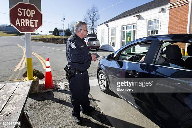 A US Customs and Border Protection agent checks the passport of a driver entering from Canada at the United States Border Inspection Station in...