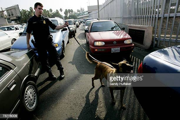 Customs and Border Protection agent Chris Burford inspects vehicles for illegal contraband with his drug sniffing dog at the U.S. Port of Entry...