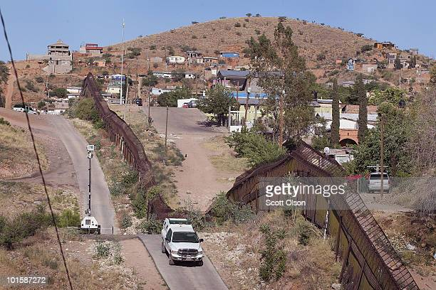 S Customs and Border Protection agent drives along a fence which separates the cities of Nogales Arizona and Nogales Sonora Mexico a frequent...