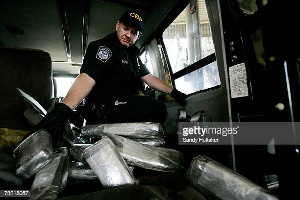 Customs and Border Protection agent Ian Bow pulls out bricks of Marijuana from a van seized at the U.S. Port of Entry December 15, 2006 in San...