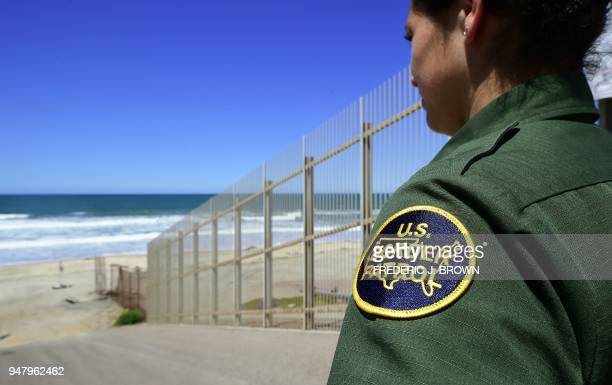 Customs and Border Protection agent looks toward the ocean from within the Border Infrastructure System a no man's land area between the wall and...