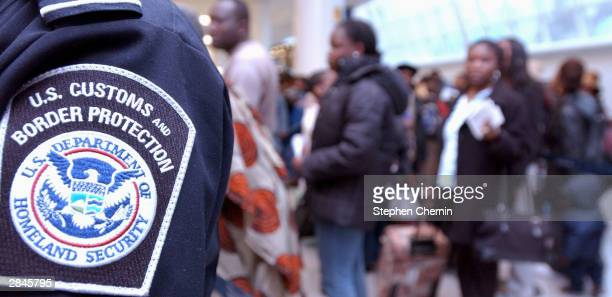S Customs and Border Protection agent stands watch as a crowd of overseas visitors to the US wait in line to pass through Customs January 5 2004 at...