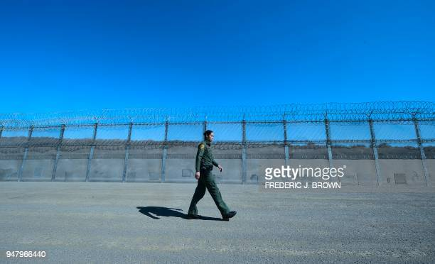 Customs and Border Protection agent Tekae Michael walks inside the Border Infrastructure System which separates the US from Mexico with a fence and...