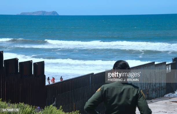 Customs and Border Protection agent watches from near the end of the border structure which runs into the Pacific Ocean in San Diego California as...