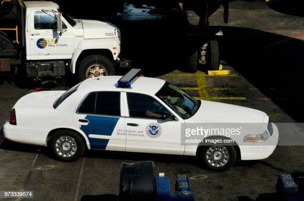 US Customs and Border Protection car with a LSG Sky Chef catering truck and the nosewheel undercarriage of an American Airlines Airbus A300600R parked