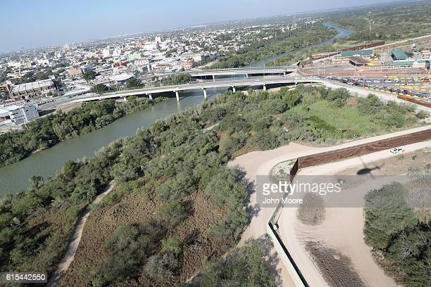 S Customs and Border Protection helicopter patrol flies over a border fence by a bridge between the United States and Mexico on October 18 2016 in...