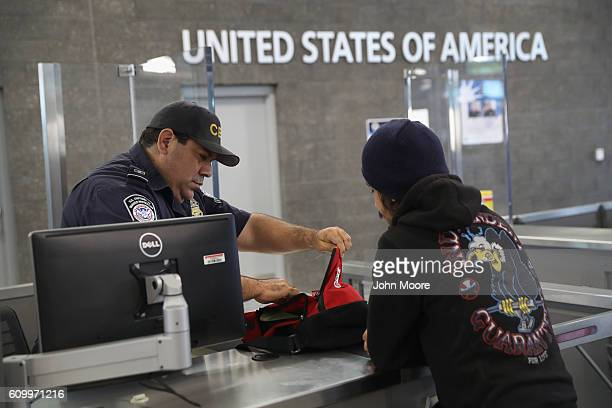 S Customs and Border Protection officer checks a backpack as people cross into the United States from Mexico on September 23 2016 in San Ysidro...