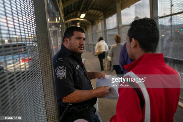 Customs and Border Protection officer checks immigration documents as a Honduran asylum seeker arrives to the international bridge from Mexico to the...