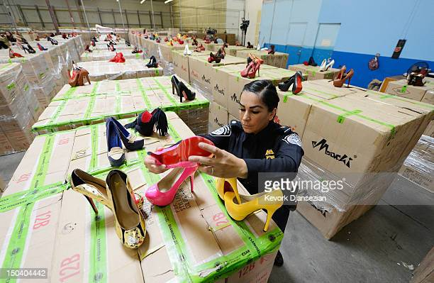 S Customs and Border Protection officer Elizabeth Ortega displays counterfeit Louboutin pumps and high heels featuring the distinctive red sole of...
