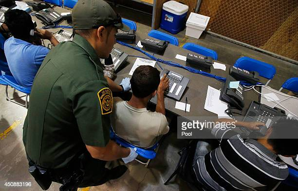 S Customs and Border Protection officer helps out a few boys who are trying to make phone calls as they are joined by hundreds of mostly Central...