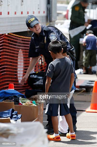 S Customs and Border Protection officer helps two young boys pick out clothes as they join hundreds of mostly Central American immigrant children as...