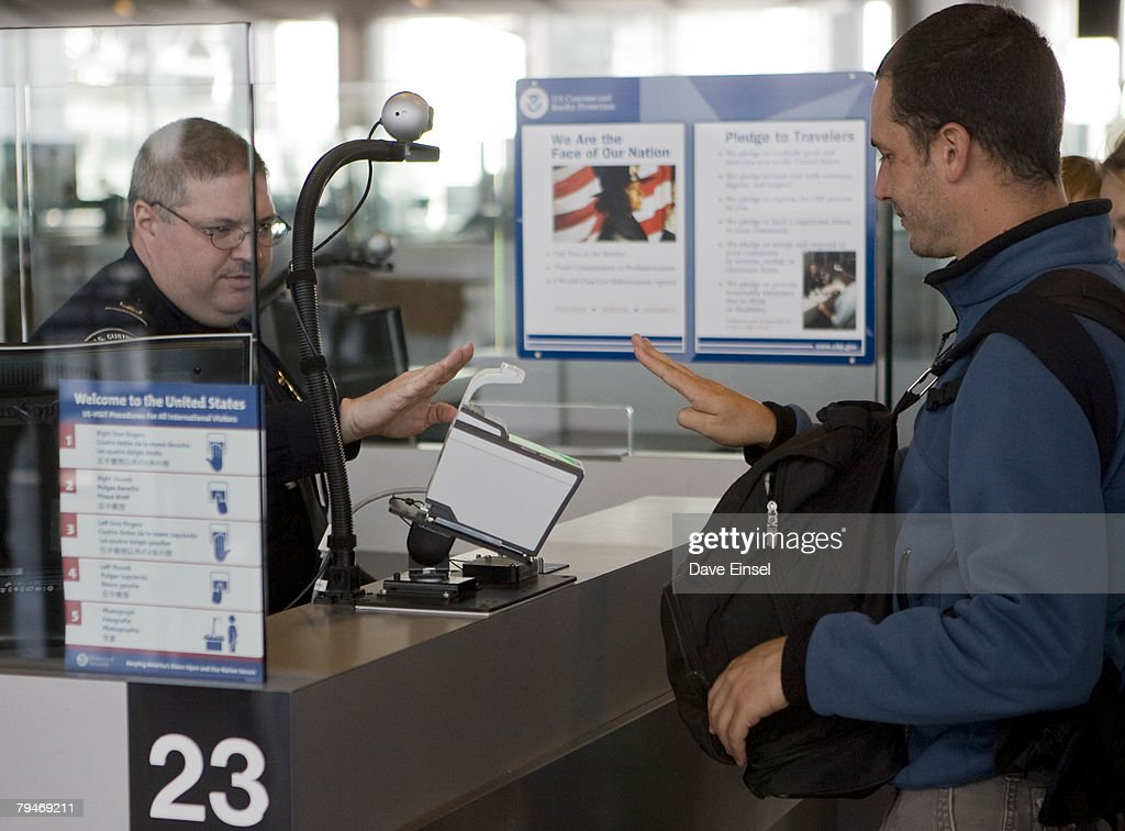 U.S. Customs and Border Protection officer Thomas Wuenschel (L) instructs an arriving passenger how to use a new biometric scanner at George H. W. Bush Intercontinental Airport February 1, 2008 in Houston, Texas. The new system is set up to scan all ten fingers instead of the two finger scanners previously used.