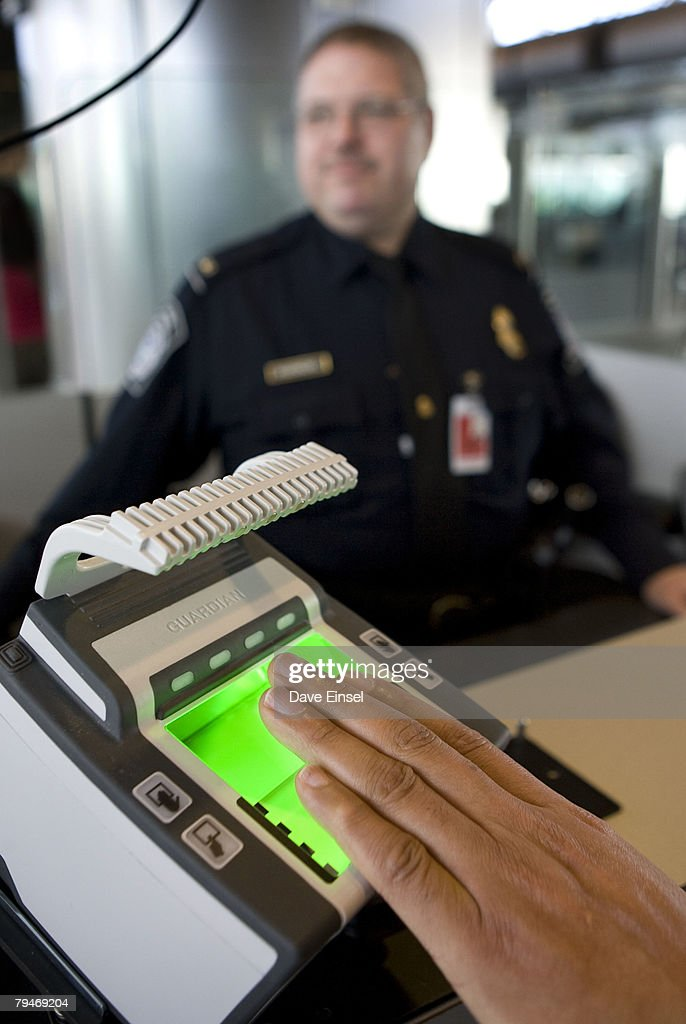U.S. Customs and Border Protection officer Thomas Wuenschel looks on as an arriving passenger uses a new biometric scanner at George H. W. Bush Intercontinental Airport February 1, 2008 in Houston, Texas. The new system is set up to scan all ten fingers instead of the two finger scanners previously used.