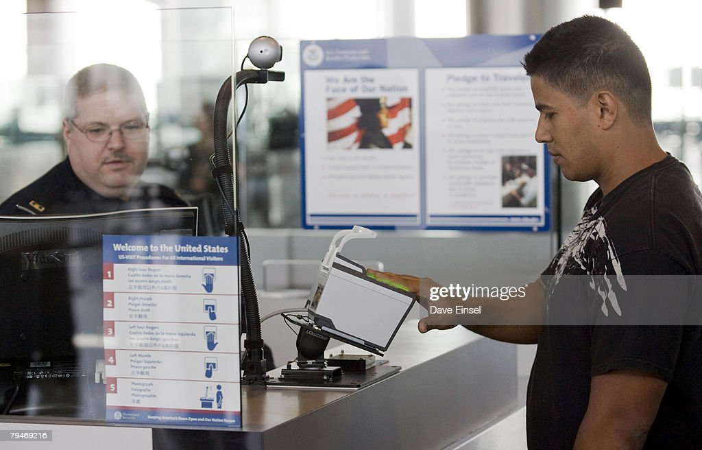 U.S. Customs and Border Protection officer Thomas Wuenschel (L) monitors his screen as an arriving passenger uses a new biometric scanner at George H. W. Bush Intercontinental Airport February 1, 2008 in Houston, Texas. The new system is set up to scan all ten fingers instead of the two finger scanners previously used.