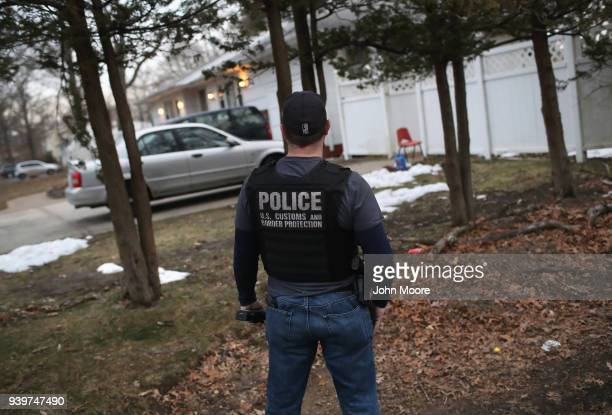 Customs and Border Protection officer watches a house as Homeland Security Investigations ICE agents detain a suspected MS13 gang member and Honduran...