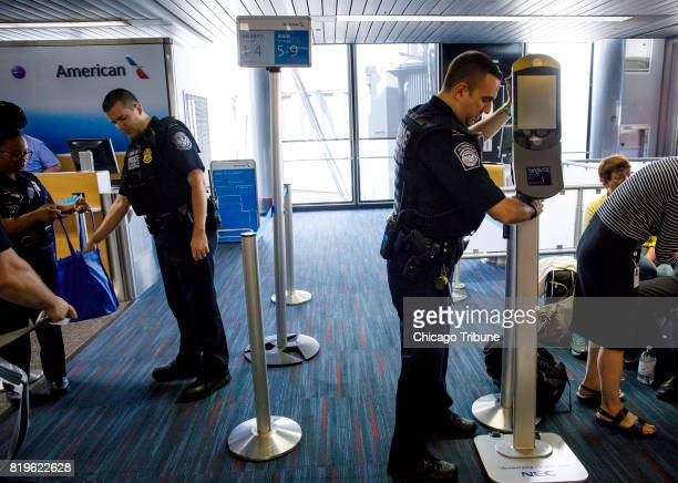 US Customs and Border Protection officers move facial recognition scanners at a gate inside Terminal 3 before an American Airlines flight to London...