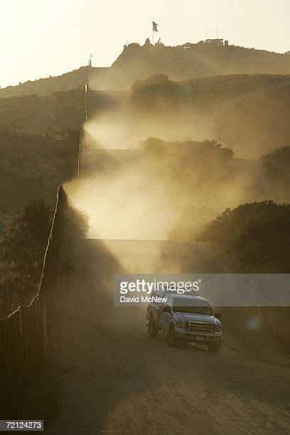 Customs and Border Protection patrol vehicle drives along the USMexico border fence in an area where activists opposing illegal immigration search...