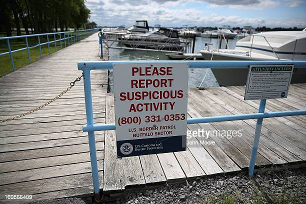 S Customs and Border Protection sign hangs on a fence at a marina on the Niagara River which forms the USCanada border on June 3 2013 in Beaver...