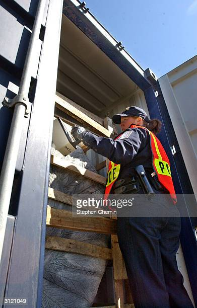 Customs inspector uses a radiation isotope identifier on freight in a shipping container during an examination at the docks March 22, 2004 in Jersey...