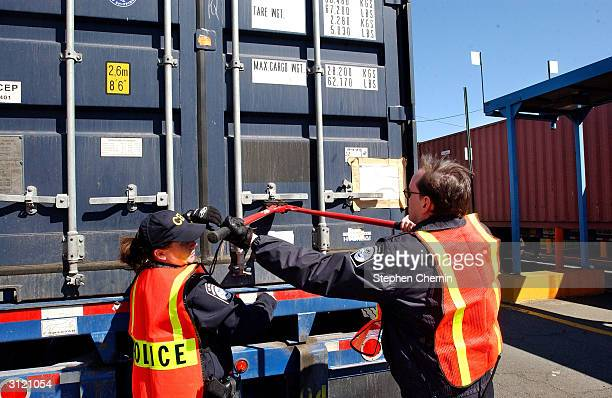 Customs inspectors cut off a lock as they prepare to examine the contents of a shipping container at the docks March 22, 2004 in Jersey City, New...