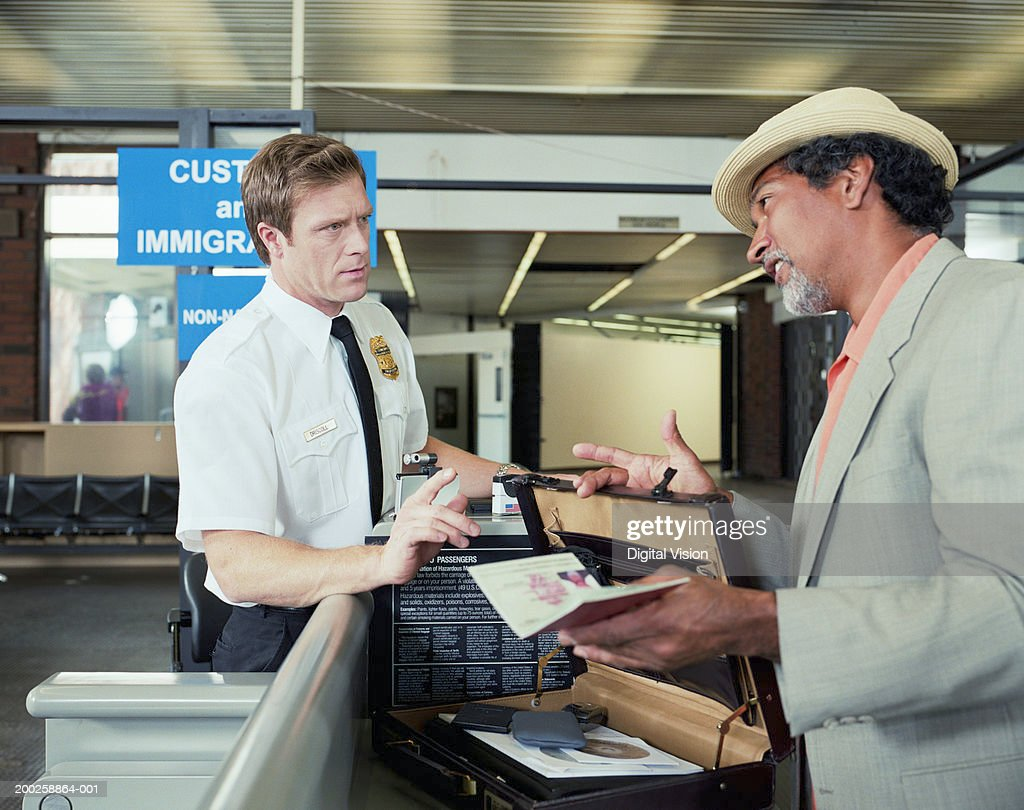 Customs officer checking man's briefcase : Stock Photo