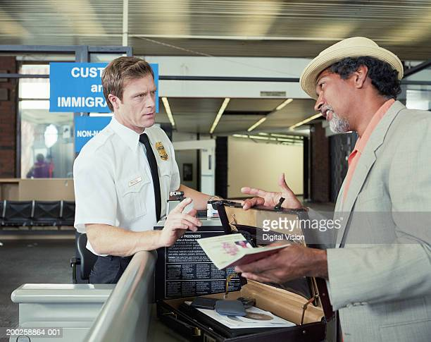 customs officer checking man's briefcase - immigration stock pictures, royalty-free photos & images