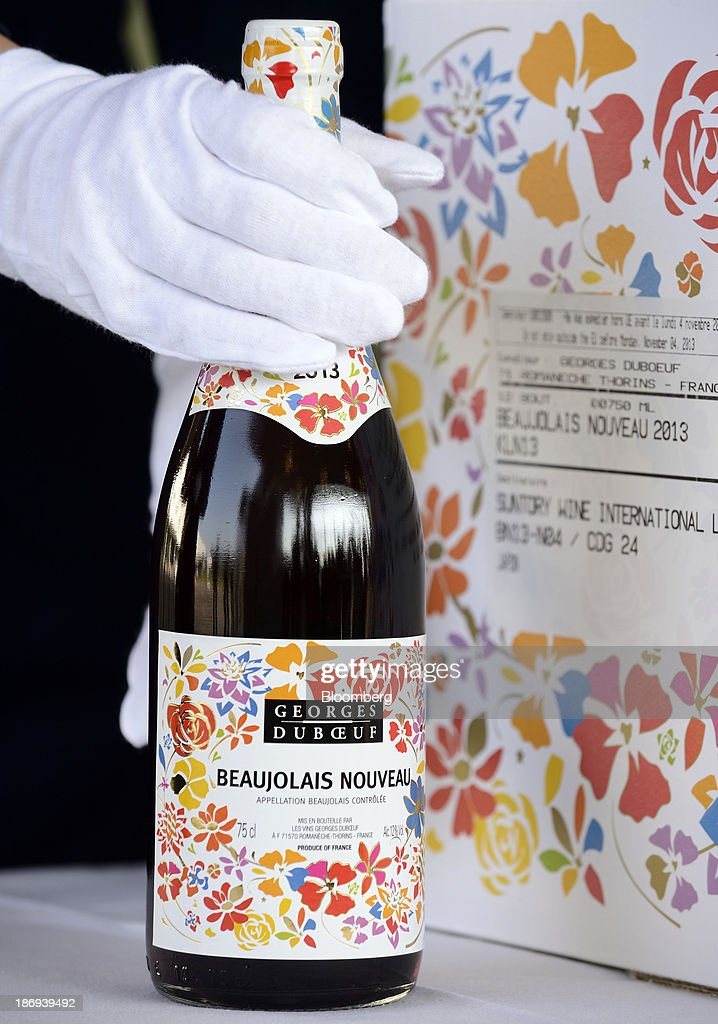 A customs officer inspects a bottle of Georges Duboeuf Beaujolais Nouveau wine at Haneda Airport in Tokyo, Japan, on Tuesday, Nov. 5, 2013. Japanese appetite for Beaujolais Nouveau has made the country the largest buyer of the young wine outside France, purchasing three times the U.S., the next biggest importer. Photographer: Akio Kon/Bloomberg via Getty Images