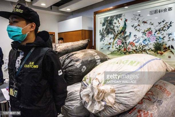 A customs officer stands in front of sacks of seized endangered pangolin scales displayed during a press conference at the Kwai Chung Customhouse...