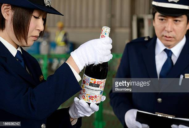 Customs officers inspect a bottle of Georges Duboeuf Beaujolais Nouveau wine at Haneda Airport in Tokyo Japan on Tuesday Nov 5 2013 Japanese appetite...