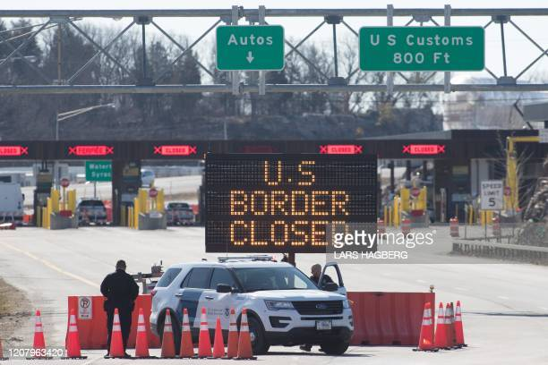 Customs officers stand beside a sign saying that the US border is closed at the US/Canada border in Lansdowne, Ontario, on March 22, 2020. - The...