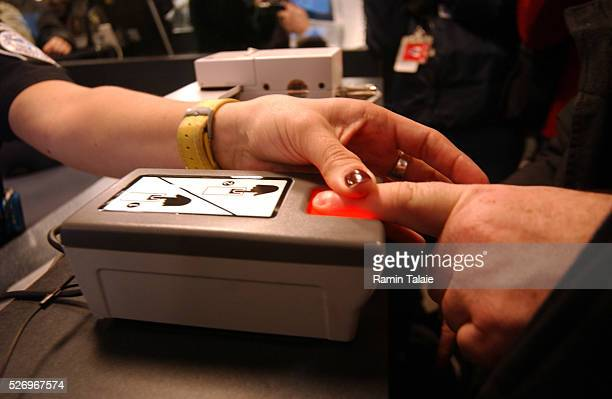 A customs official scans the finger of a foreign traveler as part of the Homeland Security Department's new program called US Visitor and Immigrant...