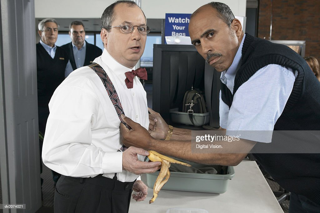 Customs Official Threatening a Man at an Airport Security Checkpoint : Stock Photo