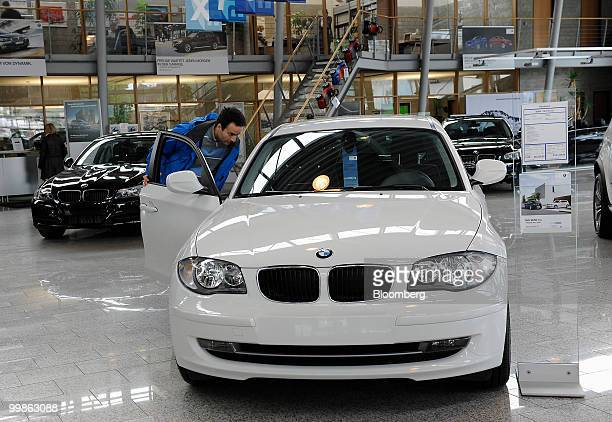 A custumer looks inside a Bayerische Motoren Werke 1 series automobile at a BMW car dealership in Rosenheim Germany on Tuesday May 18 2010 Bayerische...