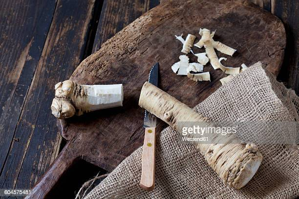 Cut and peeled horseradish on wooden board and jute