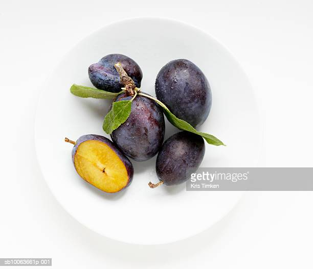 Cut and uncut plums on plate, overhead view
