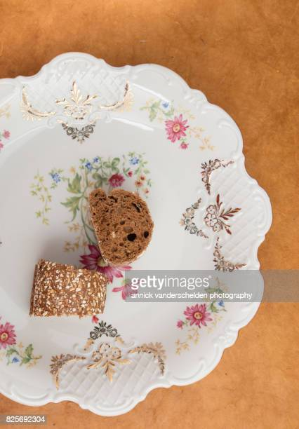 Cut baguette with pumpkin and sunflower pits piece on a decorative plate.