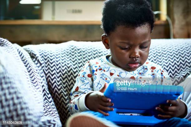 cut boy with afro hair looking at digital tablet and concentrating - using digital tablet stock photos and pictures