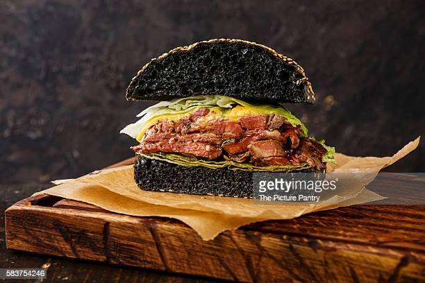 Cut in half Roast beef Burger with sliced Pastrami on dark background