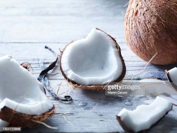 cut open coconut and vanilla on wooden surface - coconut water stock pictures, royalty-free photos & images