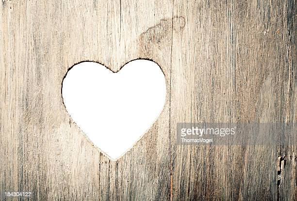 Cut out heart shape on old wood background