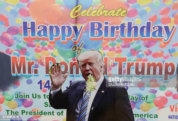A cut out of US President Donald Trump is seen with cake on his mouth after Indian activists of the right wing Hindu Sena group celebrated Trump's...