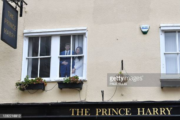 Cut out pictures of Britain's Prince Harry, Duke of Sussex and Meghan, Duchess of Sussex sit in the window of The Prince Harry pub in Windsor, west...