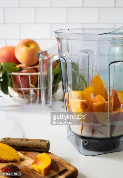 cut peaches and plant-based milk in a blender - brycia james stock pictures, royalty-free photos & images