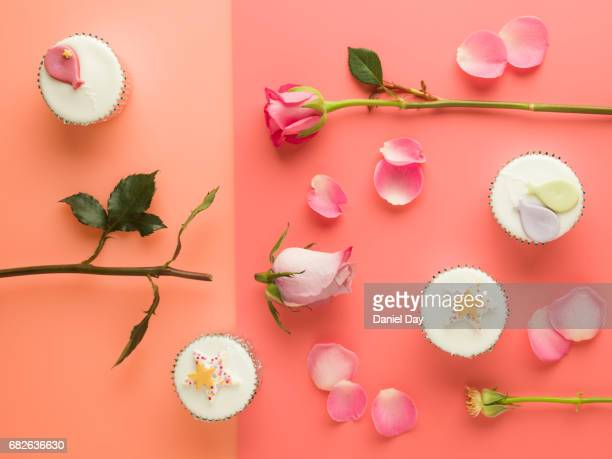 cut up pink roses lying on a split tone background with party cupcakes - peach flower stockfoto's en -beelden