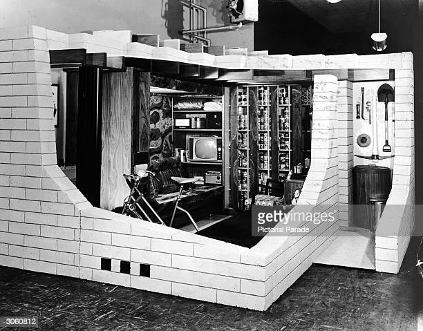 Cutaway display of a concrete masonry basement fallout shelter with an exercise bike television and library 1950s