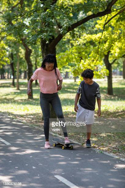 cute 10 years boy learning his mother skateboarding - 25 29 years stock pictures, royalty-free photos & images