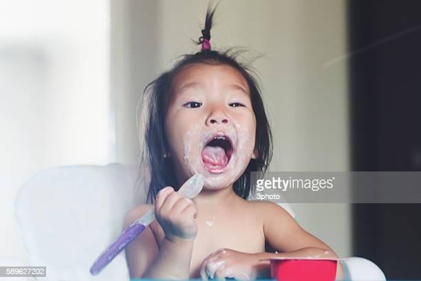 Cute 1-2 years old girl eating yoghurt