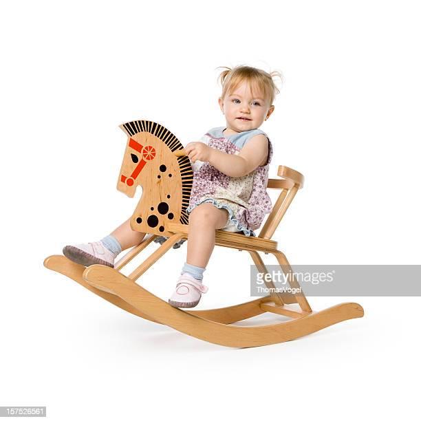 Mignon 15 mois fille sur un cheval à bascule