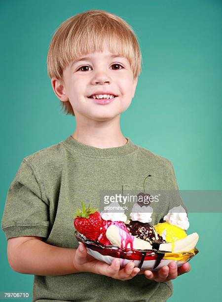 A cute 3 1/2 year old boy holding a banana split